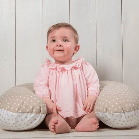 Bebe apoyada sobre una almohada de lactancia de color beige y blanco con topitos. Los cojines de lactancia sirven tambien como primer punto de apoyo cuando el bebé comienza a sentarse.