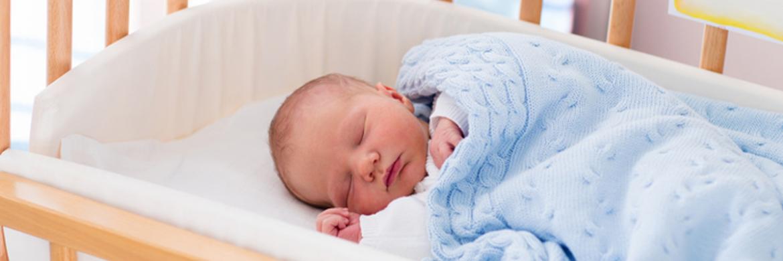 Bebe dormido sobre cuna especializada y colchón adaptado a sus necesidades