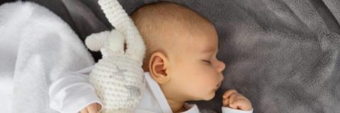 Bebé abrazado a conejito de crocket sobre manta gris. Bebé dormidito en cuna.
